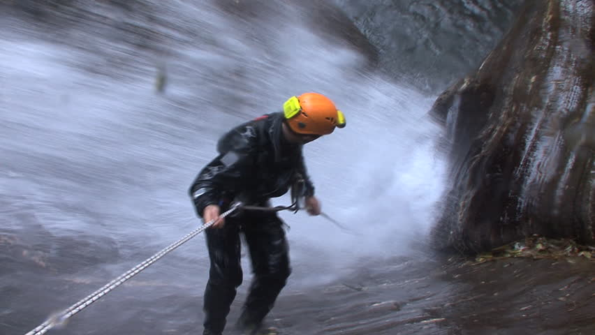 A canyoneer canyoning down a waterfall, gets hit with water, struggles while going down, top angle
