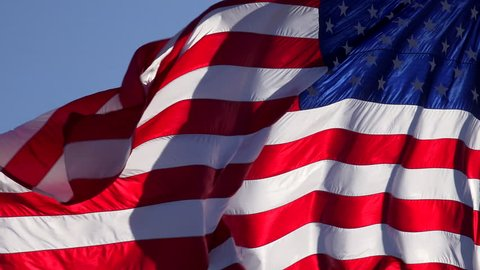 4K American flag waves free, unfurls, slowly in blue sky, light winds. 4K UHD, 3840x2160