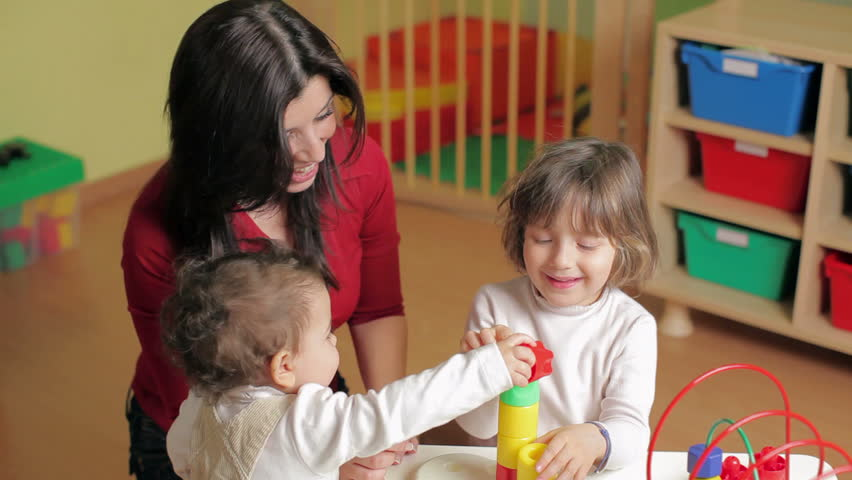 female teacher, toddler and 2-3 year girl playing with blocks toy in kindergarten