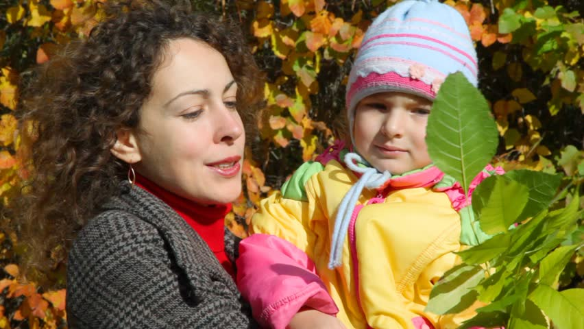 Young woman holds little girl with leaves on hands in autumn park    Shutterstock HD Video #692620