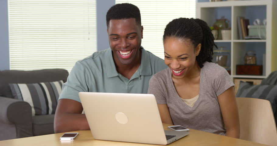Happy young black couple laughing and watching funny video on laptop | Shutterstock HD Video #6987514