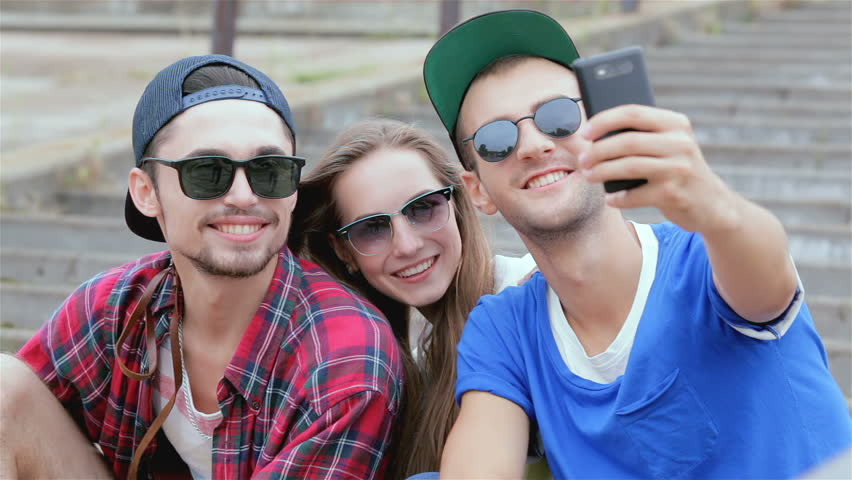 Bright and cheerful day. Young friends have fun together on the street and smile at each other. Gay threesome of friends sitting on the steps of making selfie. Slow motion.