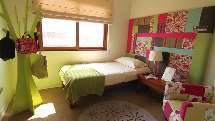 SANTIAGO, CHILE - A girl's bedroom is furnished with a single bed covered  in a