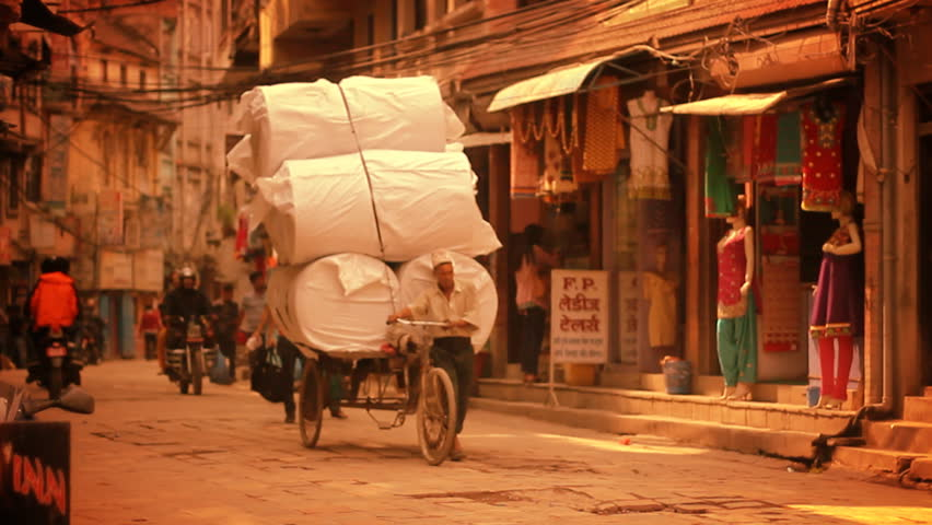 KATHMANDU, NEPAL, CIRCA MAY 2014 – Man transports large load of freight on a tricycle circa May 2014 in Kathmandu, Nepal. Kathmandu is the capital and largest urban agglomerate of Nepal.