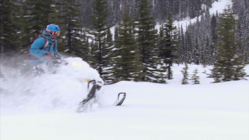 A man on a snowmobile rides through the forest in slow motion