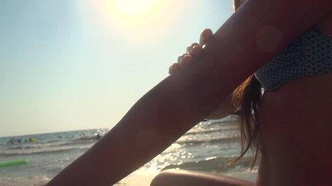 Beauty girl applying sunscreen suntan lotion from the bottle for body on the beach. Beautiful smiling happy young woman with suntan cream. Summer travel vacation. Slow motion 240 fps 1080. Sunbathing