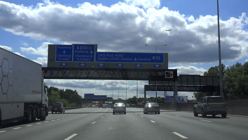M25 LONDON, HEATHROW, ENGLAND - AUGUST 2014 - POV Driving Shot of congestion on M25 Motorway - Bright Day With Blue Sky Clouds -  02666698