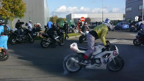 Two superbikers perform donuts while other superbikers look on and cruise along