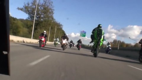 A group of superbikers ride on a freeway while doing wheelies