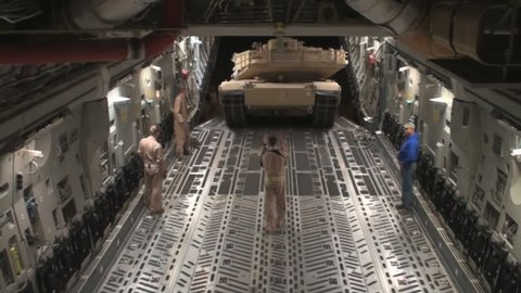 CIRCA 2010s - Airmen prepare secure and transport a USMC M1A1 Abrams tank to Afghanistan aboard a C-17 Globemaster.
