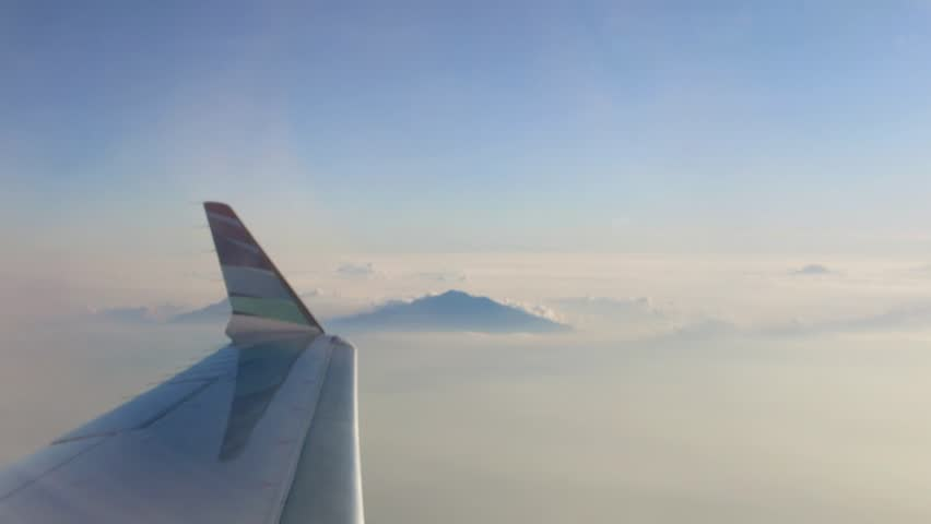 Wing of plane, flight above clouds of airplane, with mountain and sky background.