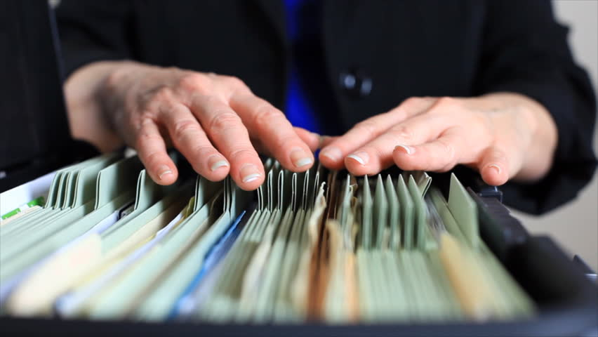 A close-up of a woman searching through a rather poor filing system.