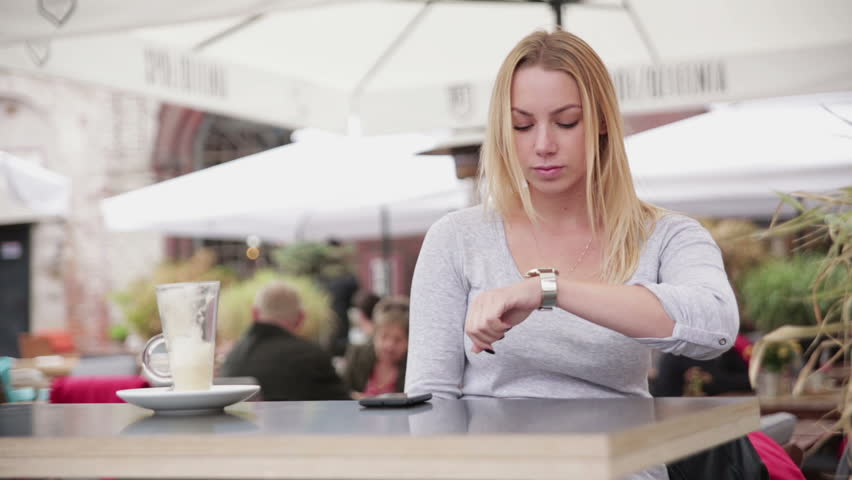 Young woman in a cafe or restaurant, she's looking at the watch and is impatiently waiting for on someone who is delayed