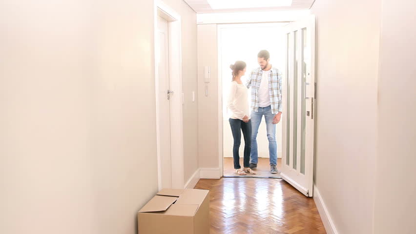 Attractive couple walking over the threshold in their new home | Shutterstock HD Video #7243204
