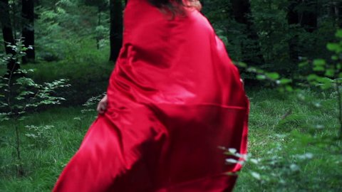 Woman in red cape run away in forest, super slow motion, 240fps