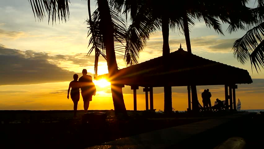 People walking at sunset, next to water house