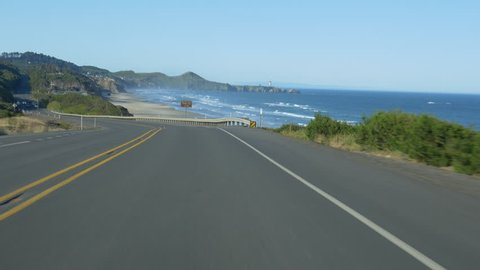 Driving on Oregon Coast Highway 101 with Yaquina Head in the background.