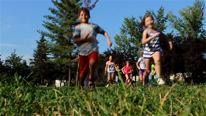 Children running in the park. Girls and boy playing on the green grass. Kids game on the playground. Teens crossing over camera in the school yard. Childhood. Blue sky. Low angle. Slow motion. 25 fps.
