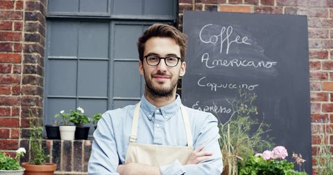 Happy barista man portrait outside cafe