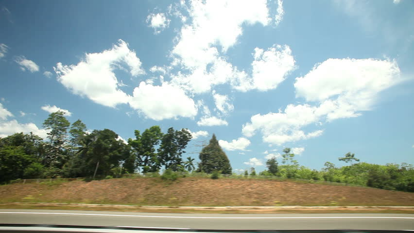 View from car window of road and countryside, with blue sky and clouds in background | Shutterstock HD Video #7372810