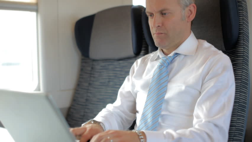 Businessman typing on laptop computer and traveling on train during rush hour