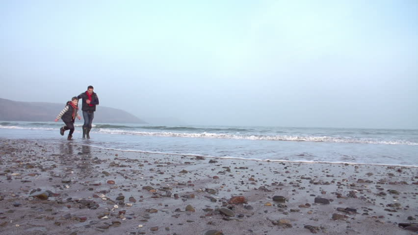 Father And Son Running On Winter Beach In Slow Motion