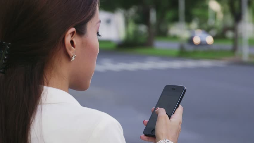 Hispanic business woman using cell phone in city street, checking e-mail and text message, cars and traffic in background. People, young manager, professions, jobs. 5of6