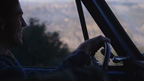 Close-up of a man driving an old pickup truck.