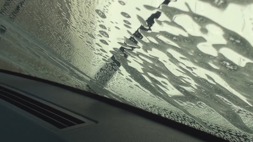 Hand washing car windshield using sponge and detergent mix with water. | Shutterstock HD Video #7394824
