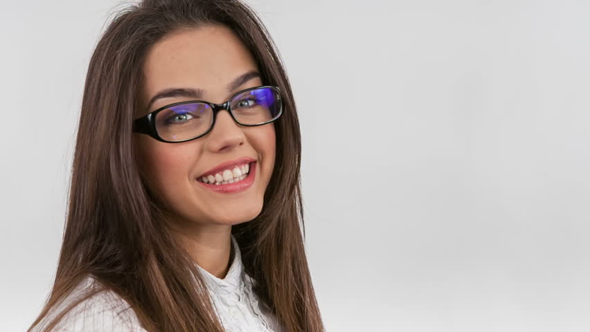 beautiful young brunette girl in nerd glasses reading a