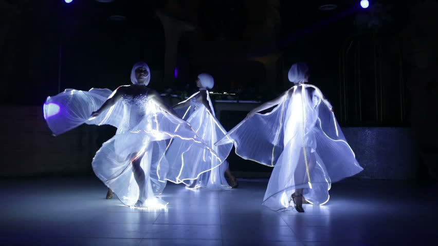 beautiful actress girl in white clothes and unusual white wigs dancing with LED wings that glow on the stage under the floodlights at night