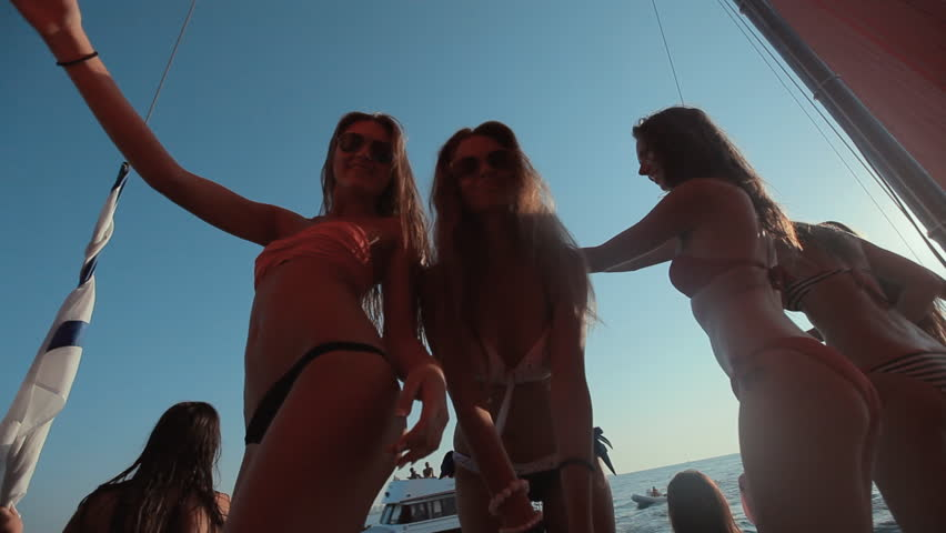 Beautiful girls in bikini relaxing on a yacht in the middle of the sea on sunset
