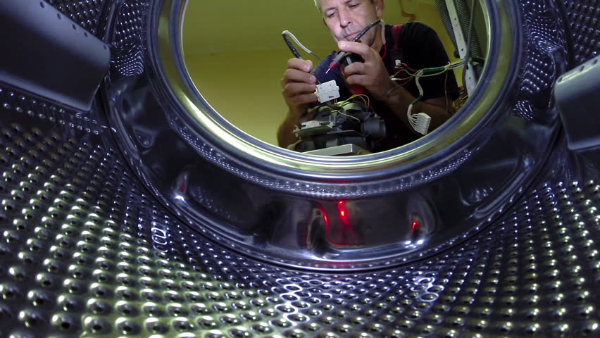 Washing Machine Repair.Repairman using digital multimeter and checking the electric motor, a view from the inside of washing machine.