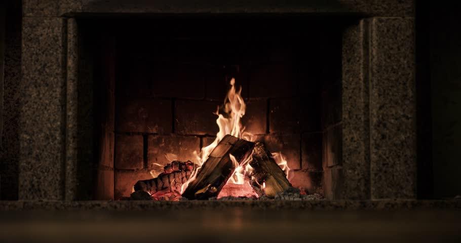 Slow motion fireplace burning. Warm cozy fireplace with real wood burning in it. Slow motion 120 fps. 4k graded from RAW.