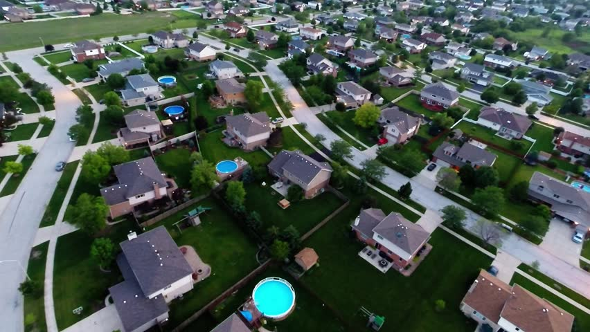 Aerial view houses in residential suburban neighborhood with backyard landscape and rooftops from air plane flight above ground