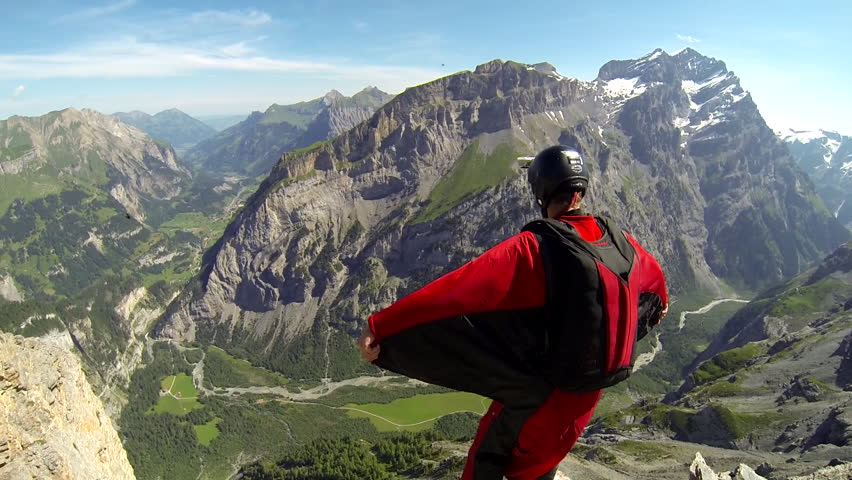 A base jumper in a wingsuit leaping off a from a rocky cliff, gliding down over a green landscape #7471381