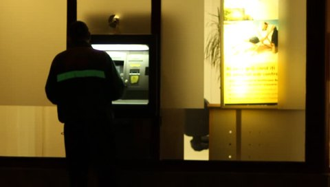 Person is using a bak ATM, by nighttime.
