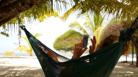 Young Woman with Curly Hair Using Mobile Smart Phone while Relaxing in a Hammock on the Beach. Exotic Island Koh Phangan. Thailand. HD, 1920x1080.