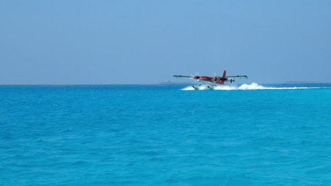 Seaplane makes landing on water. Maldives Indian Ocean.