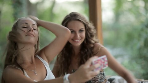 Two beautiful girls with long hair making selfie on the phone sitting in the arbor in the forest