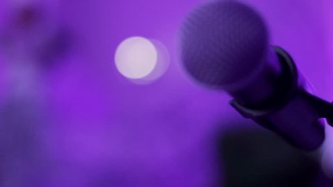 Close up of a Microphone on Stage with purple and pink lighting and blurry background.