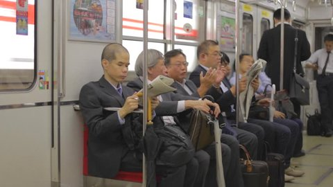 OSAKA, JAPAN - CIRCA October 2014 :Japanese businessmen talk and read newspapers on train