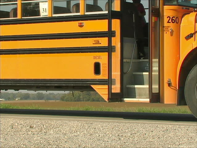 A YOUNG STUDENT JUMPS OFF THE SCHOOL BUS AFTER A LONG RIDE HOME.