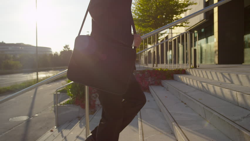 SLOW MOTION: Businessman walking up the stairs towards office building
