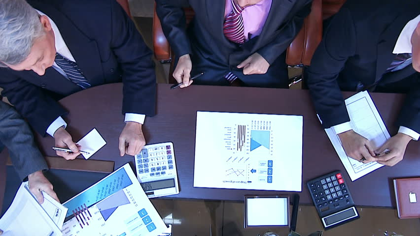 View from above. Several business people working with business papers. Graphics and drawings. See as well the hands of other people bringing documents and other business accessories   Shutterstock HD Video #7714393