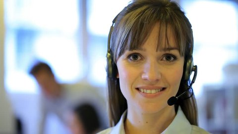 Pretty business woman talking with headset in a call center, looking camera