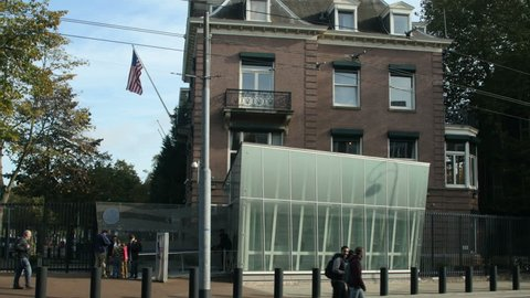 Side shot of the US Consulate in Amsterdam showing the added security entrance. US flag hangs from the building, a security guard searches a family out on the street.