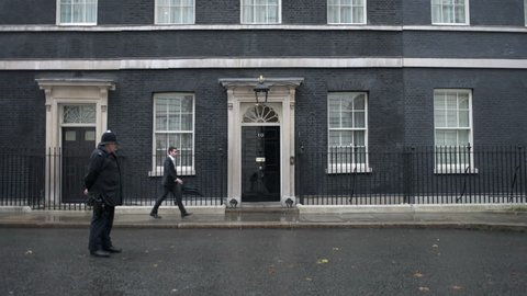 LONDON, UK - OCT 9: A police officer stands guard as a man arrives at 10 Downing Street in London on October 9, 2014