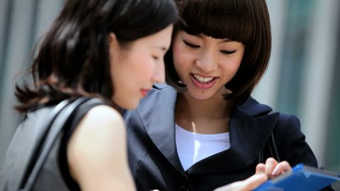 Attractive professional young American Asian Japanese females financial consultants outdoors wireless tablet communication client planning