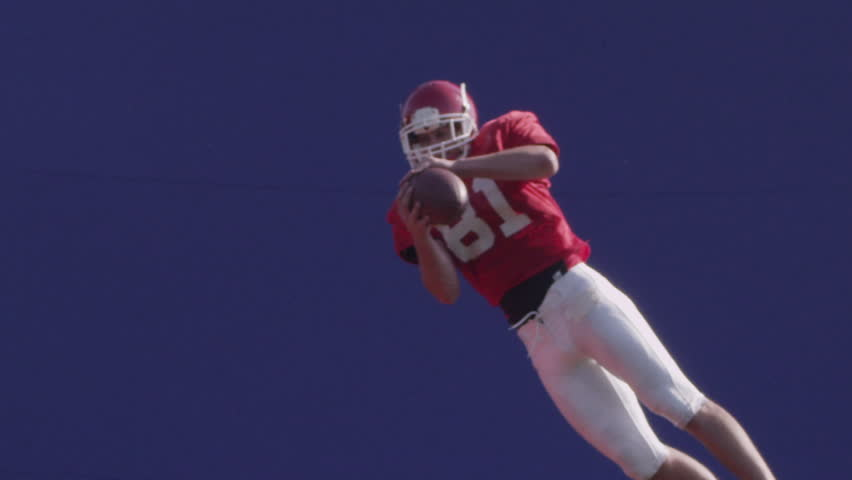 A football player catches a football in mid-air with bluescreen. HD 720p. Shot on Red One.